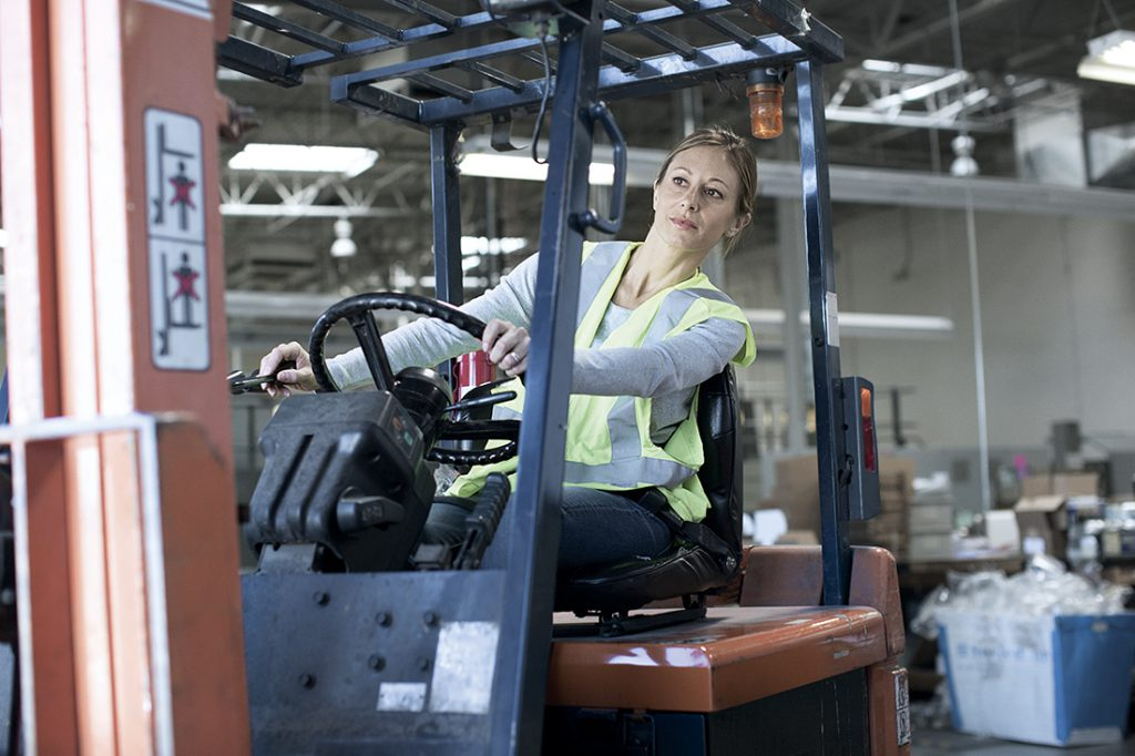 A woman in a reflective vest operating a forklift in a warehouse