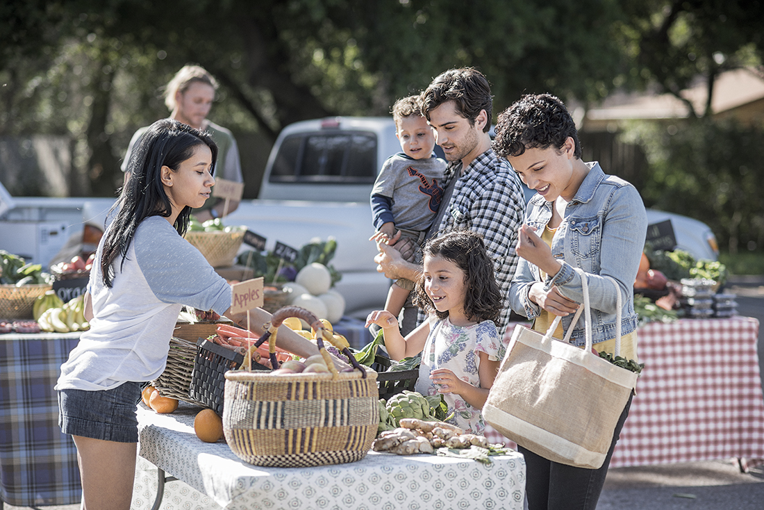 A family standing at a vendor's table at an outdoor farmer's market