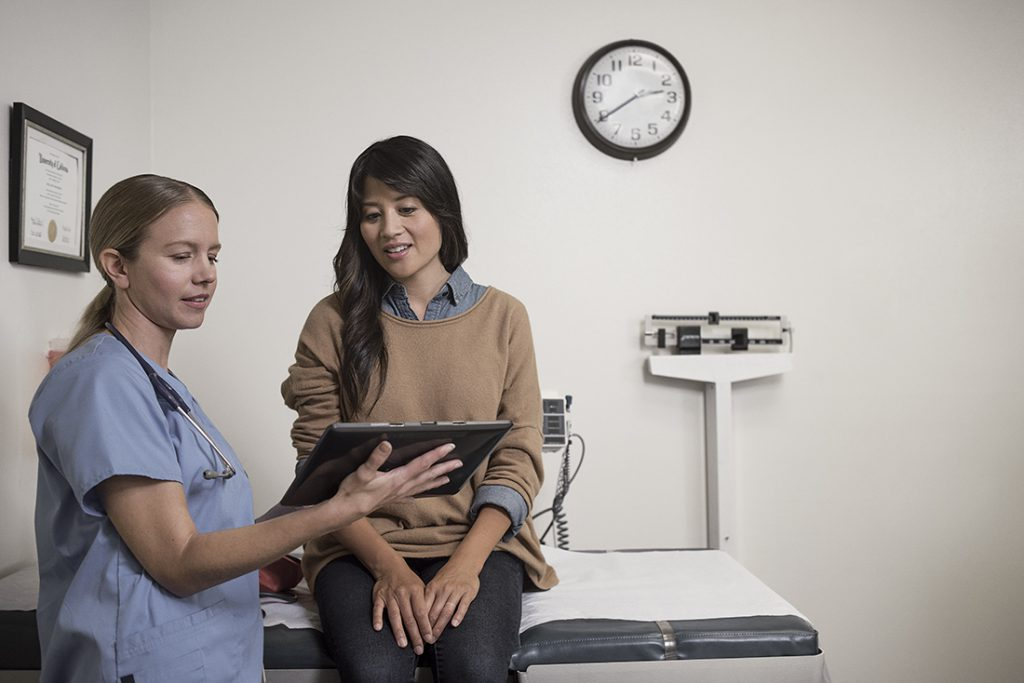 Female nurse and patient looking at a tablet in an examination room