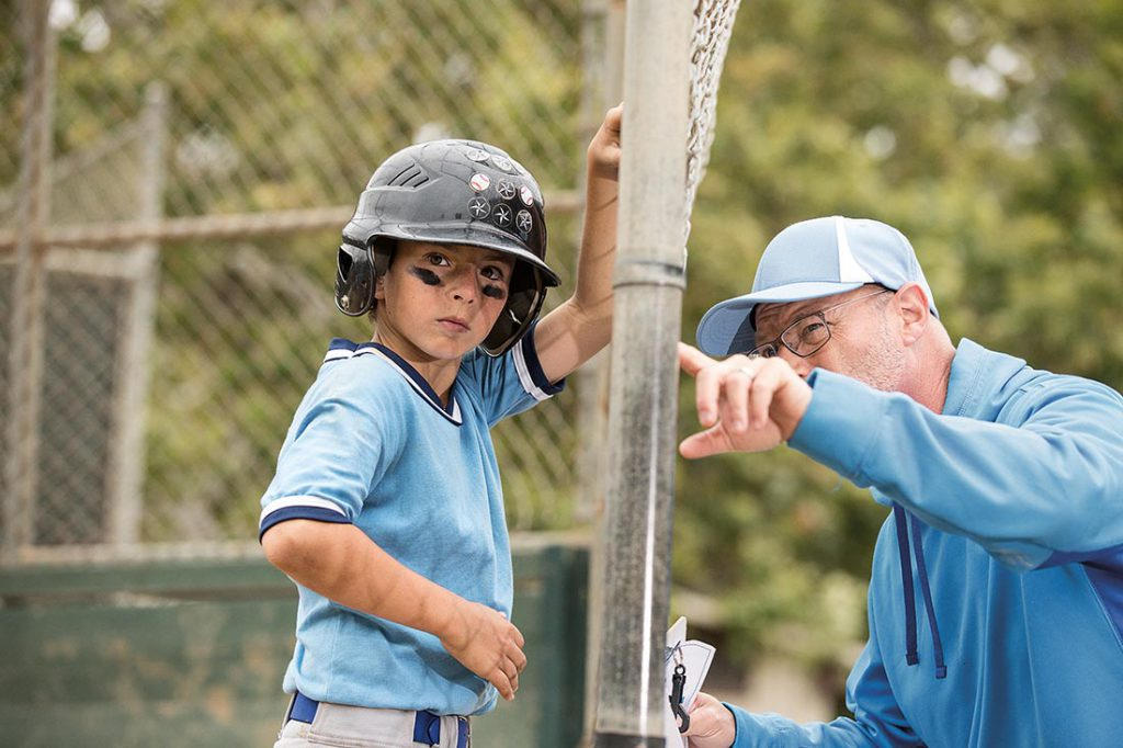 A young boy wearing a blue baseball uniform talking to a coach through a chain-link fence