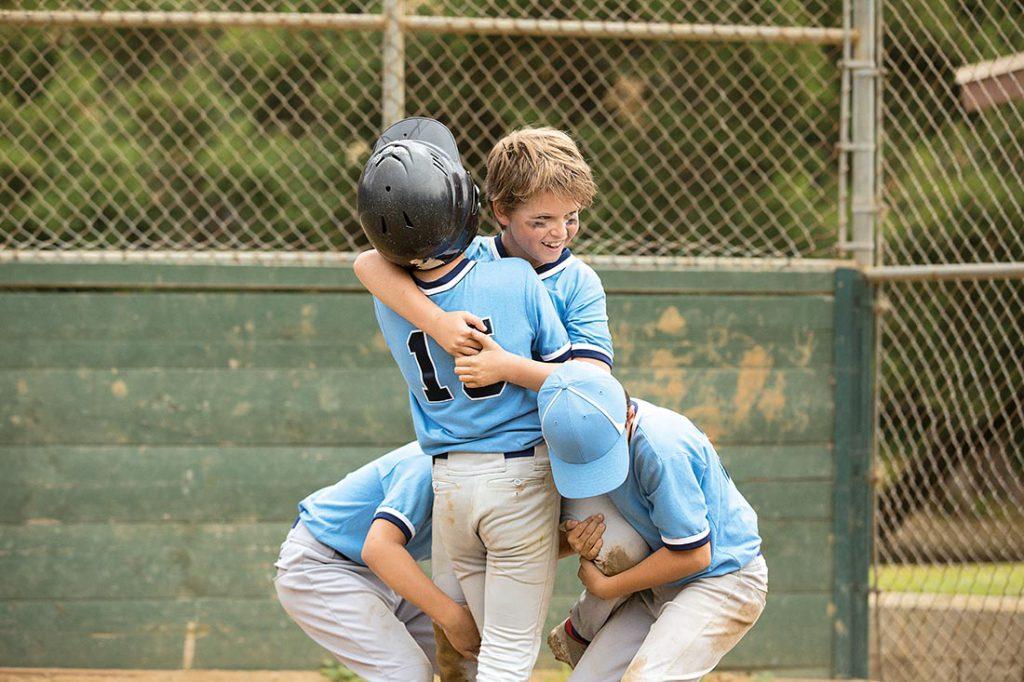 Boys wearing blue baseball uniforms hugging and celebrating
