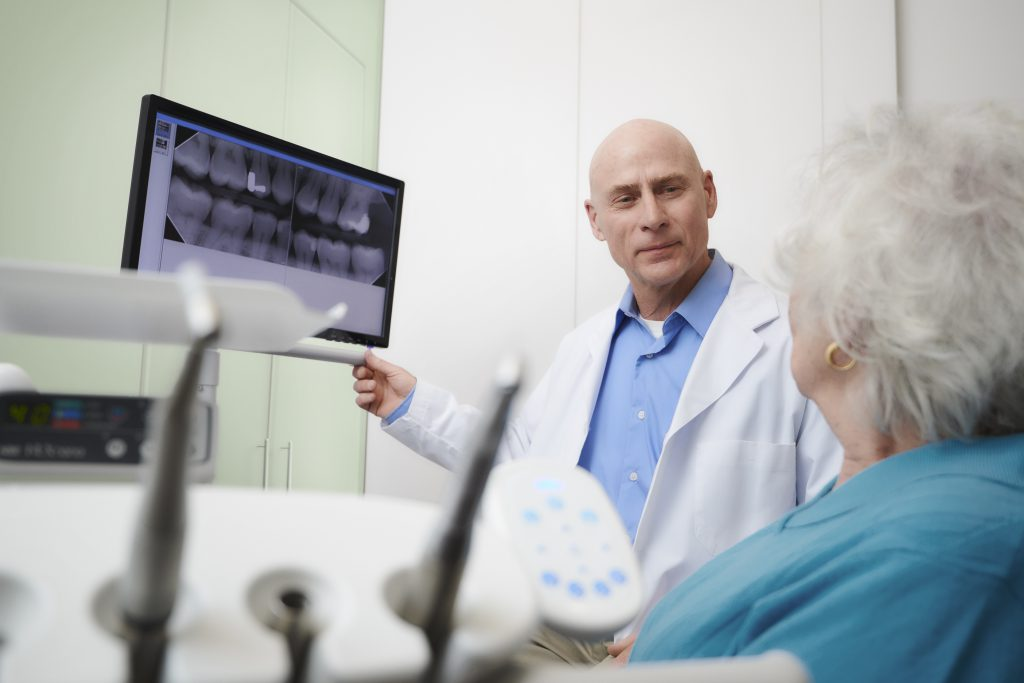 A dentist and patient discussing a dental x-ray