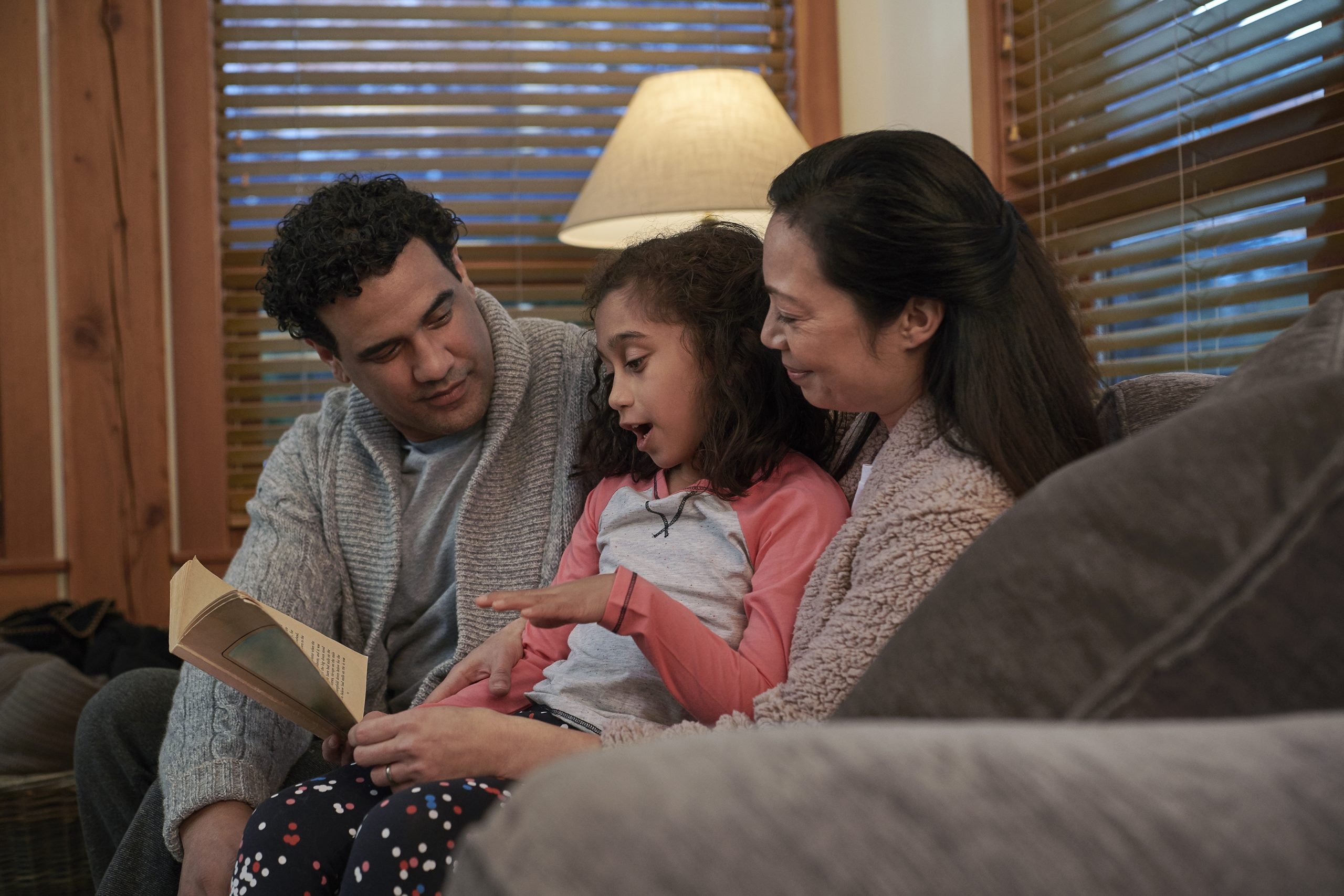A family of three reading a book on a couch