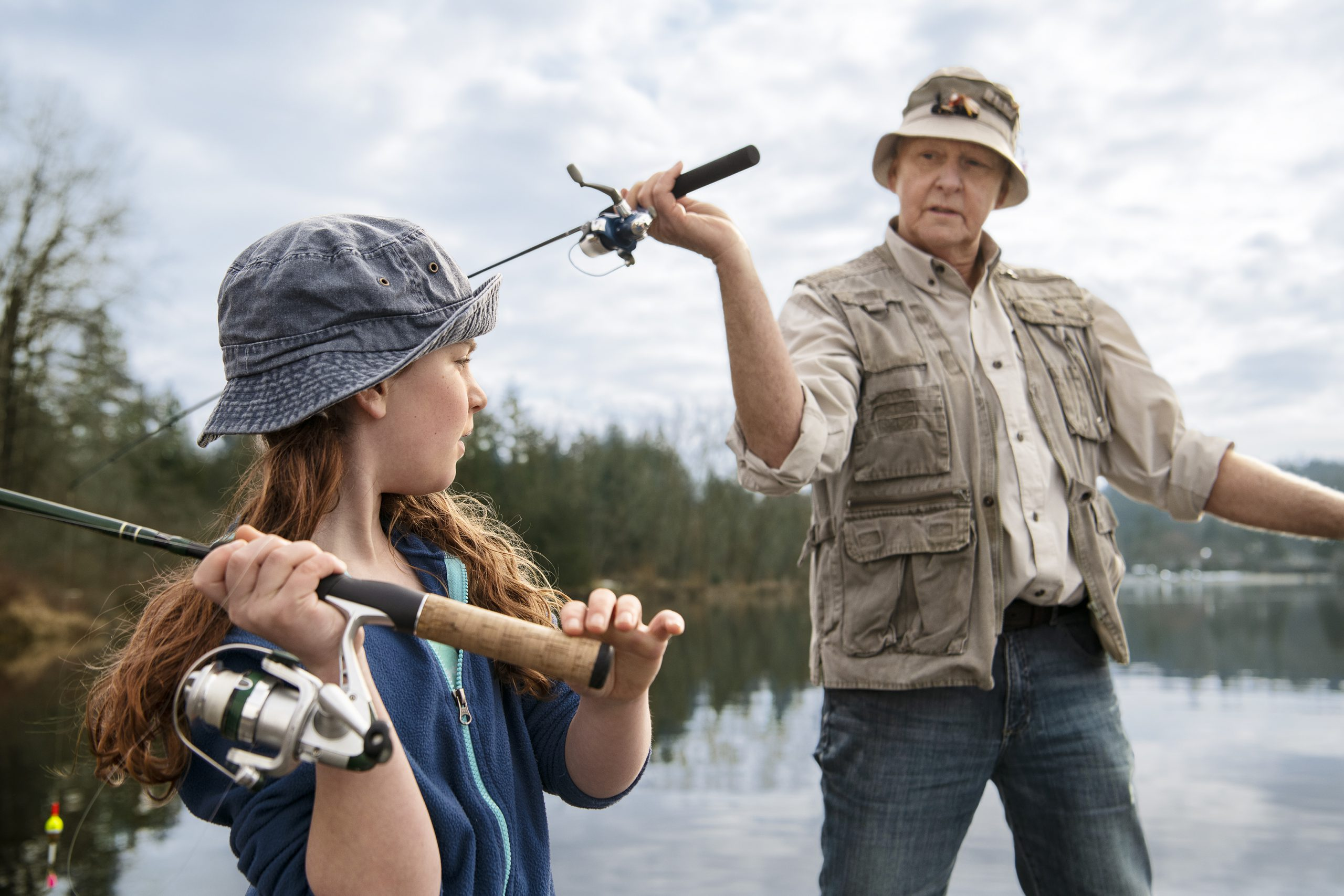 A girl and an older man casting their fishing rods on a lake