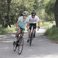 Two people riding bikes on an outdoor path