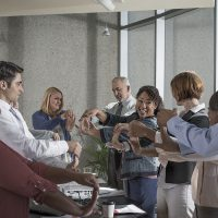 Group of adults doing wrist stretches in a conference room